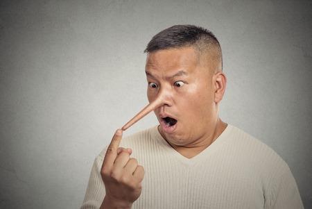 nariz: Retrato de hombre con la nariz larga aisladas sobre fondo gris de la pared. Concepto mentiroso. Expresiones faciales humanas, emociones, sentimientos Foto de archivo