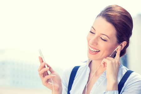 radio active: Closeup portrait attractive smiling business woman walking on street listening to music on mobile phone outdoors laughing isolated city background. Positive human emotion face expression. Urban life Stock Photo