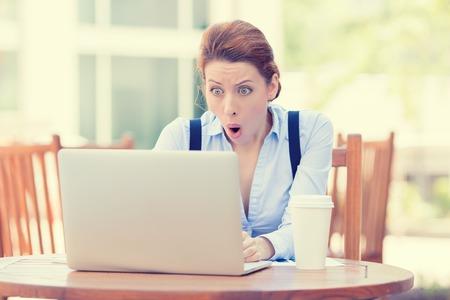 Sorprendido mujer de negocios joven usando la computadora portátil mirando la pantalla del ordenador vuelen por los estupor sentado fuera de la oficina corporativa. La expresión humana cara, emoción, sensación, percepción, lenguaje corporal, la reacción