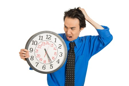 pressured: Closeup portrait business man, student, leader holding wall clock very stressed, pressured by lack of running out of time late for meeting isolated white background. Negative emotions, expressions Stock Photo