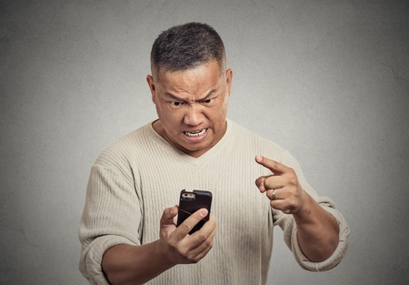 pissed off: Closeup portrait angry middle aged man, guy, mad worker, pissed off employee while on mobile, pointing with finger at his smart phone isolated grey wall background. Negative emotion facial expression