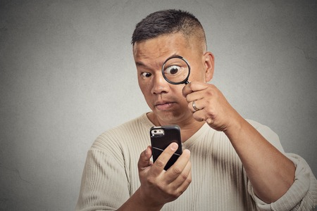 Curious business man looking through magnifying glass on smart phone isolated grey background. Human face expression. Investigator with magnifying glass. Internet Cyber security safety privacy concept photo