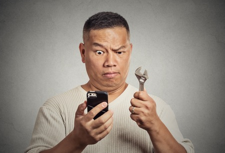 customize: Business idea solution tools concept. Businessman looking at smartphone holding wrench key instrument in hand isolated on office grey wall background. Face expression emotion. New gadget technology