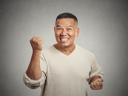 enrolled: Closeup portrait happy successful business man, employee winning, fists pumped celebrating success isolated grey wall background. Positive human emotion, facial expression. Life perception, achievement