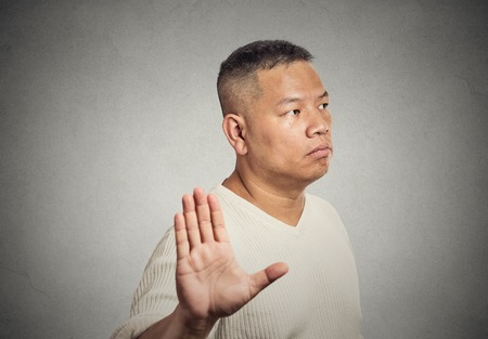 insulted: Closeup portrait grumpy middle aged man with bad attitude giving talk to hand gesture with palm outward isolated grey wall background. Negative emotion facial expression feelings body language