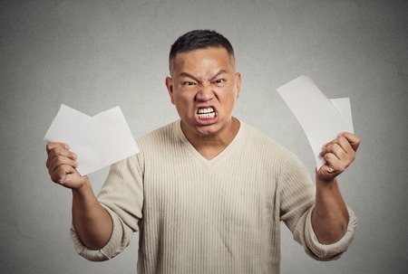 unfair: Angry frustrated middle aged man tearing business documents to pieces isolated on grey wall background. Negative human emotions, face expression, feelings, crisis