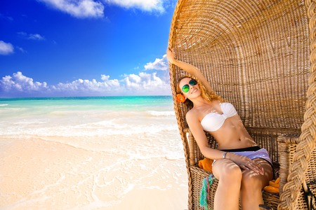 Beautiful woman young lady with sunglasses relaxing on the tropical beach enjoying sea view natural sunlight. Freedom travel vacation outdoors lifestyle leisure wellness concept photo