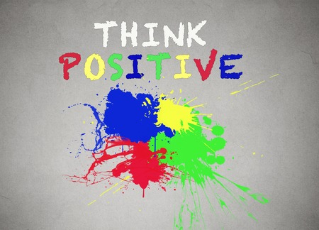 different goals: Green, blue, red, yellow splatter of paint isolated grey wall background, blackboard banner with colorful splashes think positive writing words on it. Positive life concept.