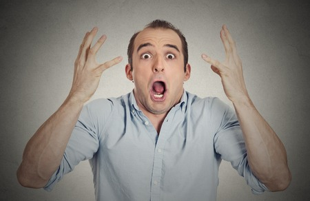 Closeup portrait headshot shocked stunned surprised young man eyes mouth wide open, hands in air yelling screaming shouting isolated grey wall background. Negative emotion facial expression feeling photo