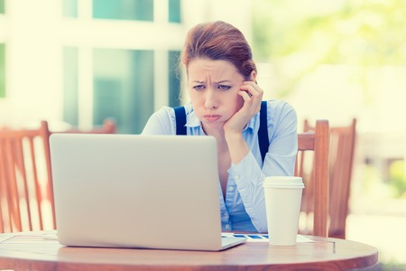 Portrait young stressed displeased worried business woman sitting in front of laptop computer isolated outdoors city background. Negative face expression emotion feelings problem perception