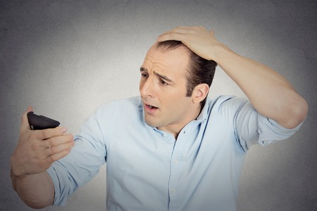 thinning: Closeup portrait shocked man feeling head, surprised he is losing hair, receding hairline or seeing bad news on cell phone isolated grey wall background. Negative facial expressions, emotion feeling Stock Photo