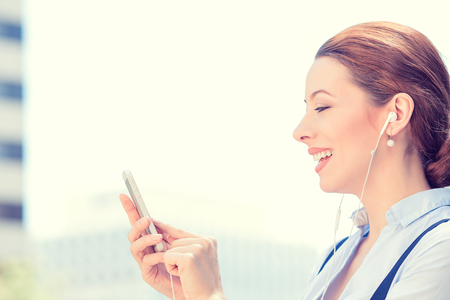 Closeup side view woman with earphones holding using smart mobile phone isolated outside corporate building background. People new generation technology concept. Customer service provider relationship photo