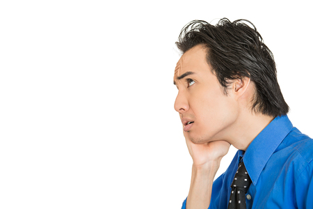 preoccupation: Worried stressed. Closeup side view portrait man, young corporate executive, worker, businessman, daydreaming, thinking looking upwards isolated on white background. Human emotions, face expression Stock Photo