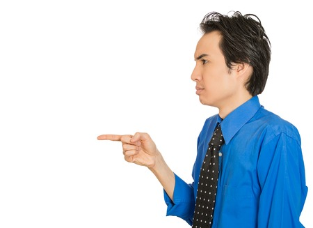 Closeup side view profile portrait serious man, pointing with index finger at someone, isolated white background space to left. Negative emotion facial expression feeling sign. Conflict resolution