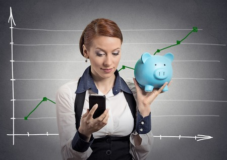 mutual funds: Closeup portrait business woman corporate employee holding piggy bank looking at smart phone isolated on grey wall office background financial chart growing up. Savings investment banking concept