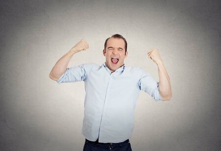 enrolled: Closeup portrait of excited, energetic, happy, screaming student, business man winning, arms up fists pumped celebrating success isolated grey wall background. Positive human emotion facial expression