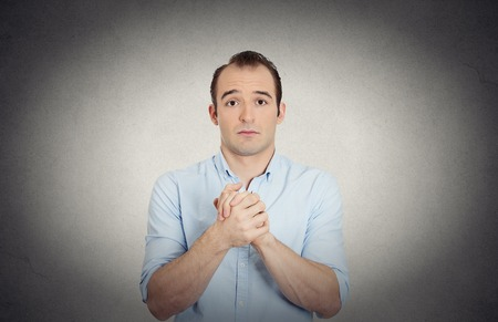 solicit: Closeup portrait desperate young man showing clasped hands, pretty please with sugar on top isolated grey wall background. Human emotion facial expression feelings, signs symbols body language