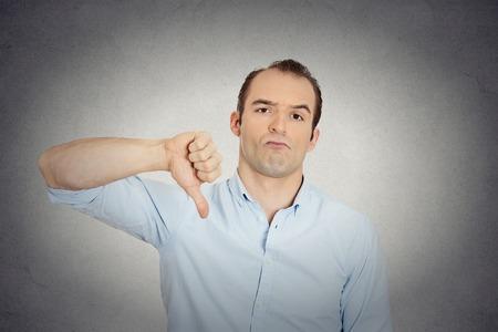 hombre pobre: Primer retrato del hombre enojado, infeliz, joven y guapo que muestra los pulgares abajo firma, en señal de desaprobación de la oferta, aislado situación fondo de la pared gris. Emoción humana Negativo sentimientos expresión facial Foto de archivo