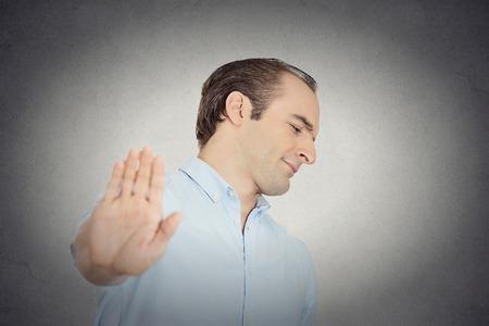 Close-up portret jonge knappe knorrige man met een slechte houding te geven bespreking aan de hand gebaar met de palm naar buiten geïsoleerde wand van de grijze achtergrond. Negatieve emotie, gezichtsuitdrukking gevoelens lichaamstaal Stockfoto