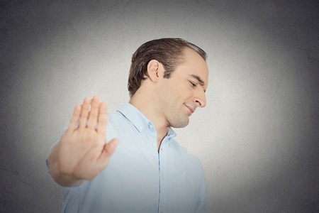 Closeup portrait young handsome grumpy man with bad attitude giving talk to hand gesture with palm outward isolated grey wall background. Negative emotion, facial expression feelings body language Standard-Bild