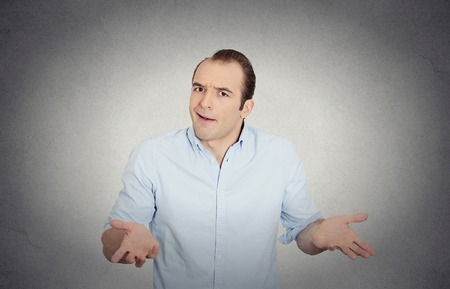 i dont know: Closeup portrait of dumb clueless funny looking young man, arms out asking whats the problem who cares so what, I dont know, isolated grey wall background. Negative human emotions facial expressions