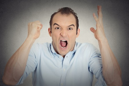 psychotic: Closeup portrait headshot angry upset young man worker mad employee funny looking businessman fist in air open mouth yelling isolated grey wall background. Negative emotion facial expression reaction Stock Photo