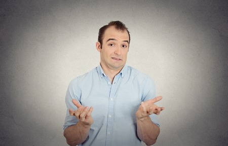 ambiguous: Closeup portrait of dumb clueless funny looking young man arms out asking what do I do now gesturing I dont know isolated grey wall background. Negative human emotion face expression body language Stock Photo