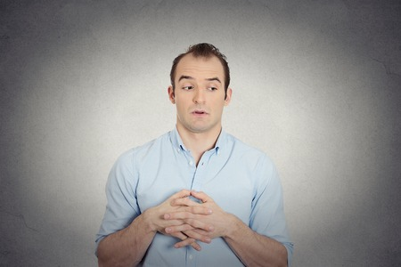 envious: Closeup portrait jealous envious, guilty, sly young business man, student employee funny guy sneakily looking aside, assessing situation isolated grey wall background. Negative human face expression