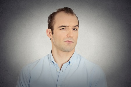 business skeptical: Closeup portrait headshot angry, mad, annoyed, skeptical, grumpy business man, employee, worker isolated grey wall background. Human emotion face expression reaction interpersonal conflict resolution Stock Photo