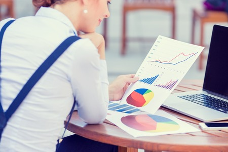 bookkeeping: woman investment consultant analyzing company annual financial report balance sheet statement working with documents graphs. Stock market, office, tax, education concept. Hands with charts papers