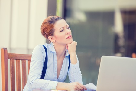 frustrated student: Portrait young stressed displeased worried business woman sitting in front of laptop computer isolated outdoors city office background. Negative face expression emotion feelings problem perception
