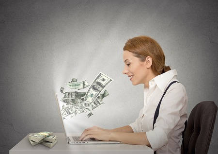 cash back: Side profile happy smiling business woman working online on computer earning money dollar bills banknotes flying out of laptop screen isolated grey wall office background. Human face expression Stock Photo
