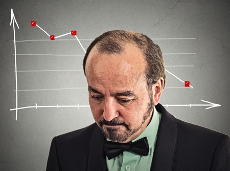 deprived: Headshot depressed stressed business man looking down financial market chart graphic going down on grey office wall background. Poor economy crisis meltdown loss concept. Face expression emotion Stock Photo