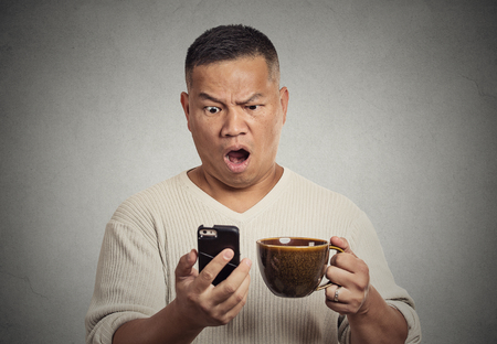 breakup: Closeup portrait shocked surprised middle aged man with wide open mouth reading breaking news on smart phone, holding cup of coffee isolated grey wall background. Human face expression emotion
