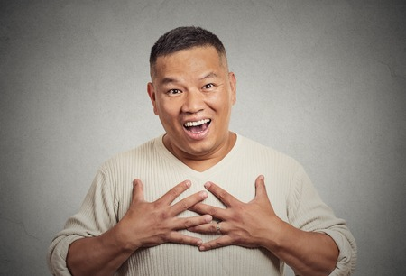 expression: Closeup portrait happy middle aged handsome man looking shocked surprised in disbelief hands on chest open mouth eyes isolated grey wall background. Positive human emotion facial expression feeling