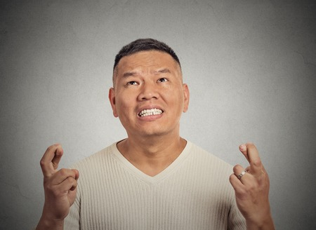 crossing fingers: Closeup portrait young funny guy, middle aged man crossing fingers, wishing, hoping for best miracle isolated grey wall background. Positive human emotion face expression feeling attitude anticipation Stock Photo