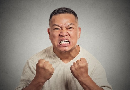 body language: Closeup portrait headshot angry middle aged man with open mouth fist up in air aggressive screaming isolated grey wall background. Negative human emotion face expression feeling body language reaction