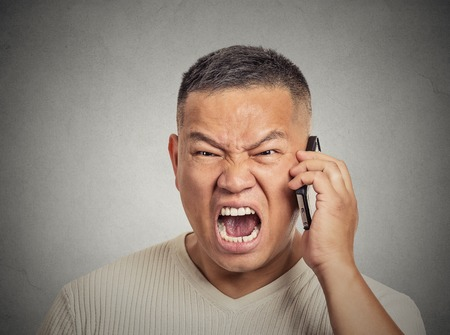 pissed off: Closeup portrait headshot angry middle aged man, guy mad worker, pissed off employee shouting while on phone isolated grey wall background. Negative human emotion face expression feeling attitude Stock Photo