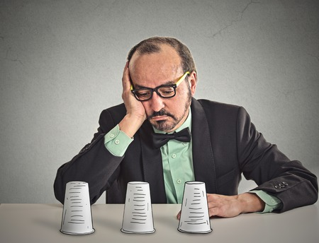 games of chance: Desperate sad middle aged business man with glasses sitting at desk looking down playing a conjuring trick game isolated grey wall office background. Human face expression. Gambling risk concept Stock Photo