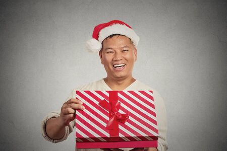 captivated: Closeup portrait happy excited surprised middle aged man opening unwrapping red gift box isolated grey wall background, enjoying his present. Positive human emotion facial expression feeling attitude Stock Photo