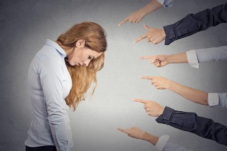 Concept d'accusation d'affaires coupable. Side portrait de profil femme triste bouleversé regardant vers le bas de doigts pointant à son bureau isolé gris fond. Visage humain sentiment expression de l'émotion