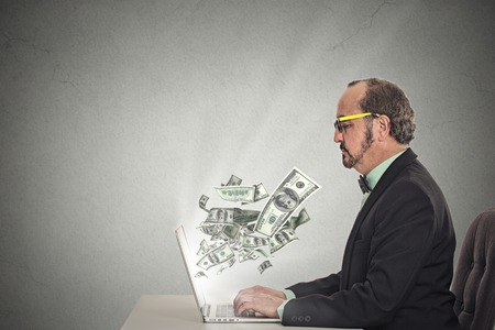 internet sale: Side profile corporate business man with glasses working online on computer earning money dollar bills banknotes flying out of laptop screen isolated grey wall office background. Human face expression Stock Photo