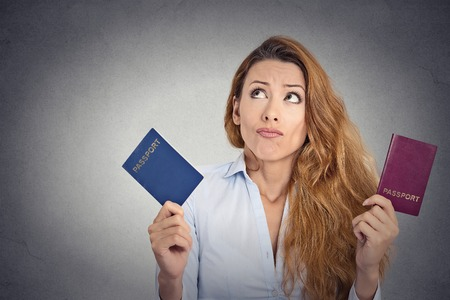 Portrait young woman holding two passports confused face expression isolated on grey wall background Foto de archivo