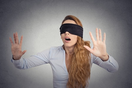 ojos vendados: Joven empresaria caminar con los ojos vendados con las manos adelante aisladas sobre fondo gris de la pared