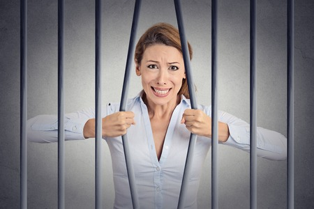prison break: Stressed desperate angry businesswoman bending bars of her prison cell grey wall background. Life limitations, law violation infringement tax evasion consequences concept. Face expression emotion