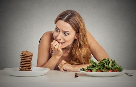 comida chatarra: Mujer joven del retrato de decidir si va a comer alimentos saludables o dulces galletas que ella está anhelando sentado en mesa aislado fondo de la pared gris. Reacción cara expresión emoción humana nutrición concepto de dieta