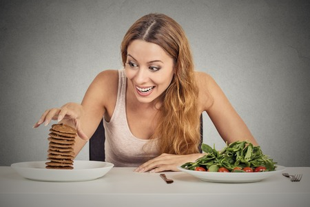 obsessed: Portrait young woman deciding whether to eat healthy food or sweet cookies she is craving sitting at table isolated grey wall background. Human face expression emotion reaction Diet nutrition concept