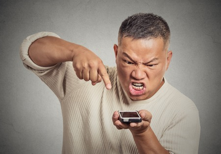 Closeup portrait angry middle aged man, guy, mad worker, pissed off employee while on mobile smart phone isolated grey wall background. Negative emotion facial expression Stock Photo