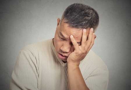 bothered: Closeup portrait headshot sad bothered stressed middle aged man holding head with hand really depressed about something isolated grey wall background. Negative human emotion facial expression feeling