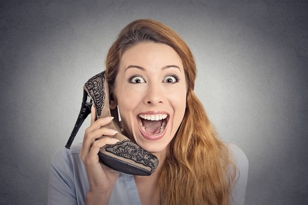high heeled shoe: Headshot young happy woman looking excited, holding an high heeled shoe in her hand as a phone isolated on grey wall background. human face expression emotion feelings